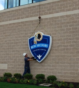Dickie Saunders of Holiday Signs positions the new stadium identification sign on the wall in Richmond.